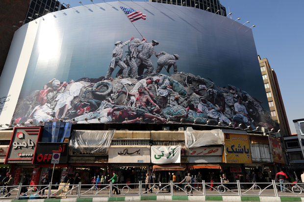 "A picture taken on January 18, 2016 shows an anti-US banner inspired by American photographer Joe Rosenthal's iconic World War II photograph ""Raising the Flag on Iwo Jima"" displayed on a building in the capital Tehran. / AFP / ATTA KENARE"