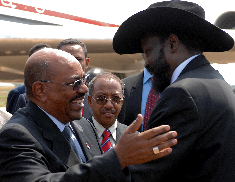 Sudanese President Omar Hassien Al Bashr hug South Sudan President Salva Kiir