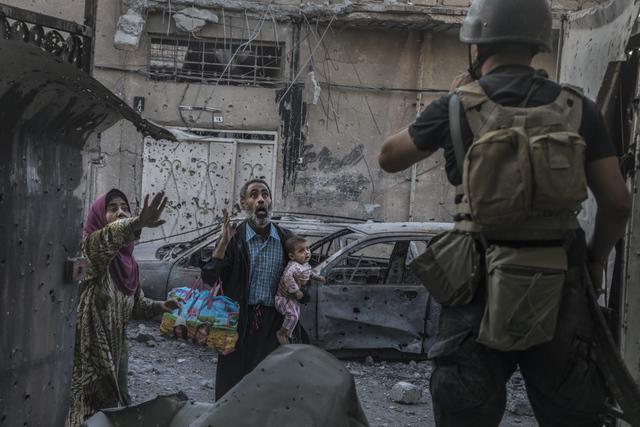 Mossoul, Irak, le 02/06/2017 Un commando de 7 hommes de la 1re brigade des forces spŽciales irakiennes combat Daesh maison par maison pour prendre le contr™le de Sakha, un des derniers quartiers de Mossoul ˆ tre encore tenus par le groupe Etat Islamique au nord de la vieille ville. Un des Humvees de la brigade vient d'essuyer un tir de RPG et le tireur est recherchŽ dans les Žtages des maisons. Les hommes sont tendus, les combattants ennemis n'hŽsitent pas ˆ faire des attaques suicides et sur les trois maisons reprises en une heure, 2 Žtaient piŽgŽes. Le dŽmineur systŽmatiquement placŽ en tte du commando vient de jeter une grenade dans la pice suivante pour la traverser. Elle donne sur la cour arrire, et soudainement, dans les explosions de bombes et les tirs nourris de la rue, ce ne sont pas des combattants de Daesh qui font apparaissent mais des civils en panique. Photo Laurent Van der Stockt pour Le Monde