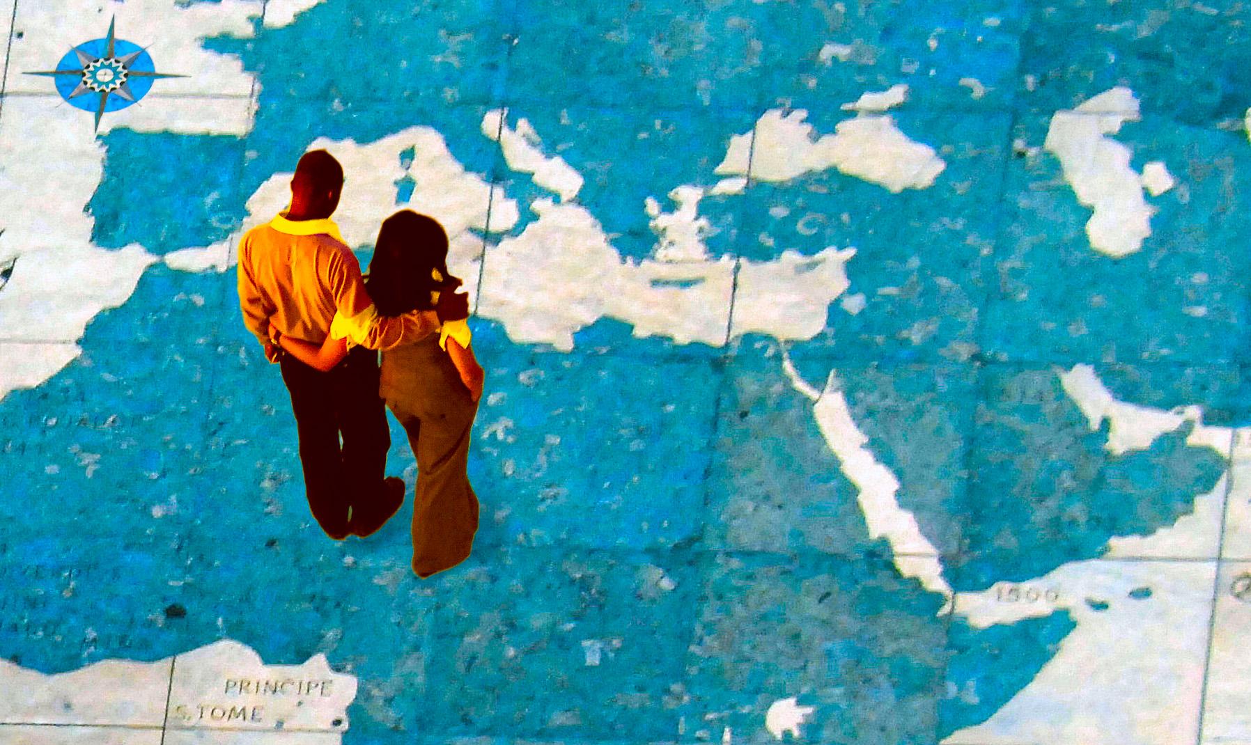 Un homme et femme sur un planisphère géant regardent le Moyen-Orient