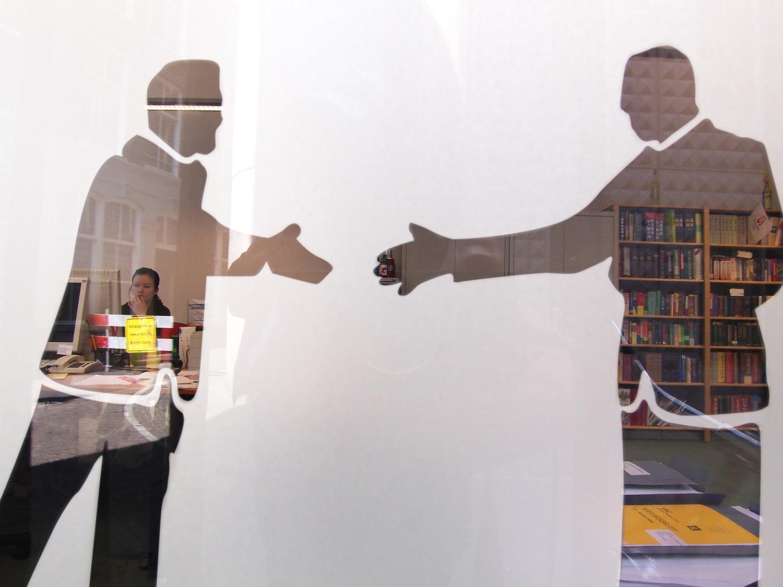 La silhouette de deux personnes se serrant la main sur une vitrine