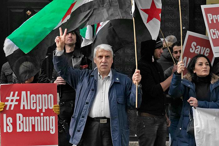 """Un vieil homme tient un drapeau syrien d'une maine et fait le V de la victoire de l'autre main. Une pancarte à côté de lui : """"Aleppo is burning"""""""
