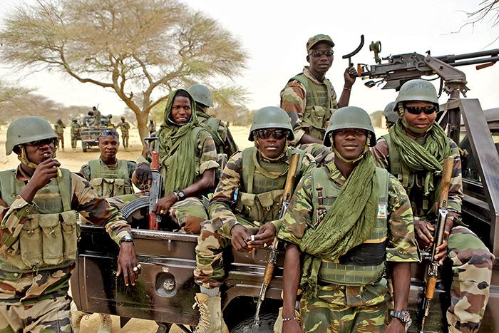 Un groupe de soldats nigériens posent à l'arrière d'un pick-up.