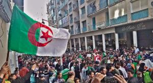 Foule qui brandit un drapeau algérien.