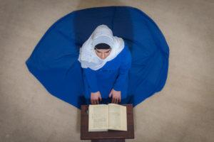 Vue aérienne d'une femme voilée agenouillée devant un livre saint.