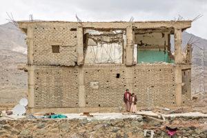 Un homme adulte et son fils adolescent sont début devant un immeuble touché par les bombardements aériens. Derrière eux il y a un paysage montagneux aride au Yémen