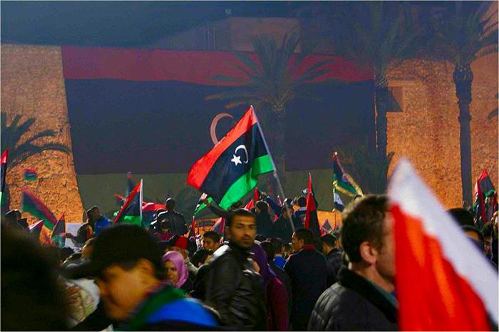 Une foule brandit des drapeaux libyiens.