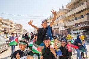 Foule d'enfants dans une rue, tenant des drapeaux palestiniens. En premier plan un jeune garçon sur les épaules d'un autre garçon fait le signe de la victoire de ses deux mains.