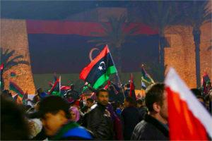 La place des Martyrs à Triplo, des hommes brandissent des drapeaux libyens. On voit un immense drapeau sur un mur en arrière fond de l'image.