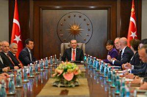 Le président turc Erdogan assis à une table ovale lors d'un meeting organisé par le dépazrtement du commerce des États-Unis