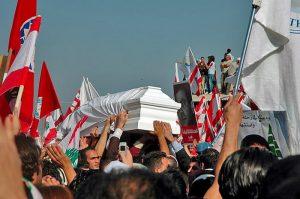 Une foule tient à bout de bras un cercueil blanc. De nombreux drapeaux libanais sont brandis.