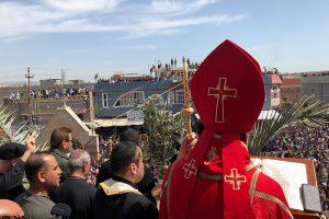 Le pape et des hommes de dos, tournés vers un village irakien.