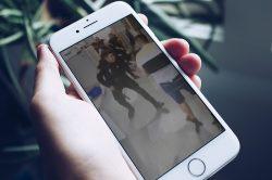 main avec téléphone portable qui montre à l'écran un policier israélien qui frappe un palestinien
