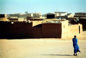 Sahraoui avec vêtement traditionnel bleu avec les maisons du champ de réfugiés de Tindouf sur le fond
