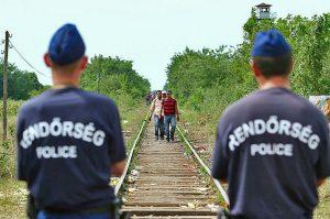 Deux policiers de dos sur des rails de train. Des migrants arrivent en marchant en face d'eux.