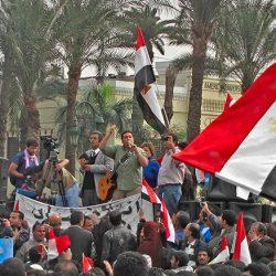 Un chanteur avec une guitare sur un estrade incite la foule lors d'une manifestation en Égypte
