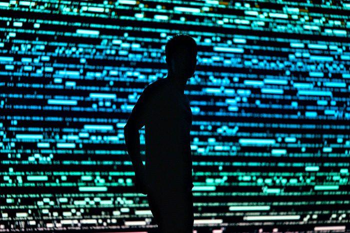 Homme en contrejour sur fond de données numériques