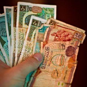Main qui tient des billets de banque syriens