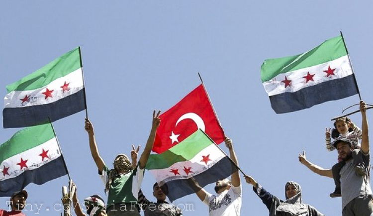 Syrian refugees wave Turkish and Syrian Independence flags during a protest against Assad at Yayladagi refugee camp in Hatay province on the Turkish-Syrian border April 10, 2012.