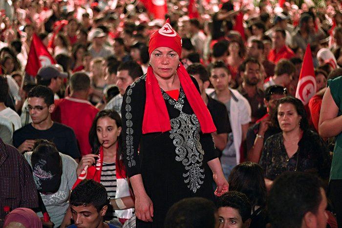 Femme débout au milieu de manifestants avec des drapeaux de la Tunisie portant un drapeau de la Tunisie en foulard