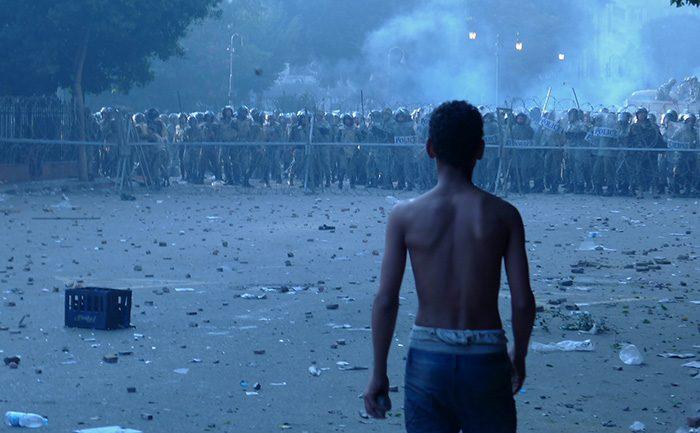 Jeune en Égypte se tient débout devant une file de policiers